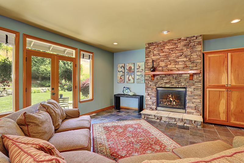 Cozy living room with blue walls, tile floor and stone tile fireplace.