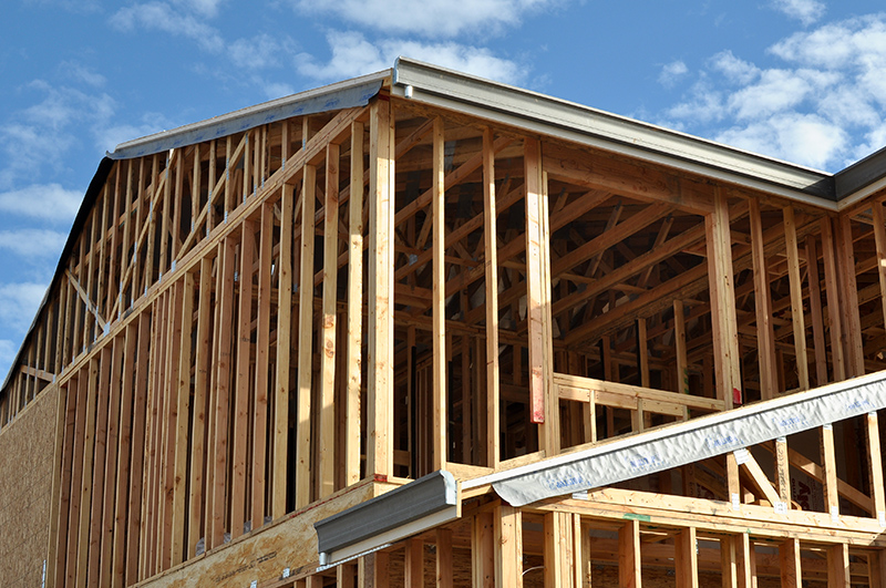 New home construction site showing wooden beam house structure.